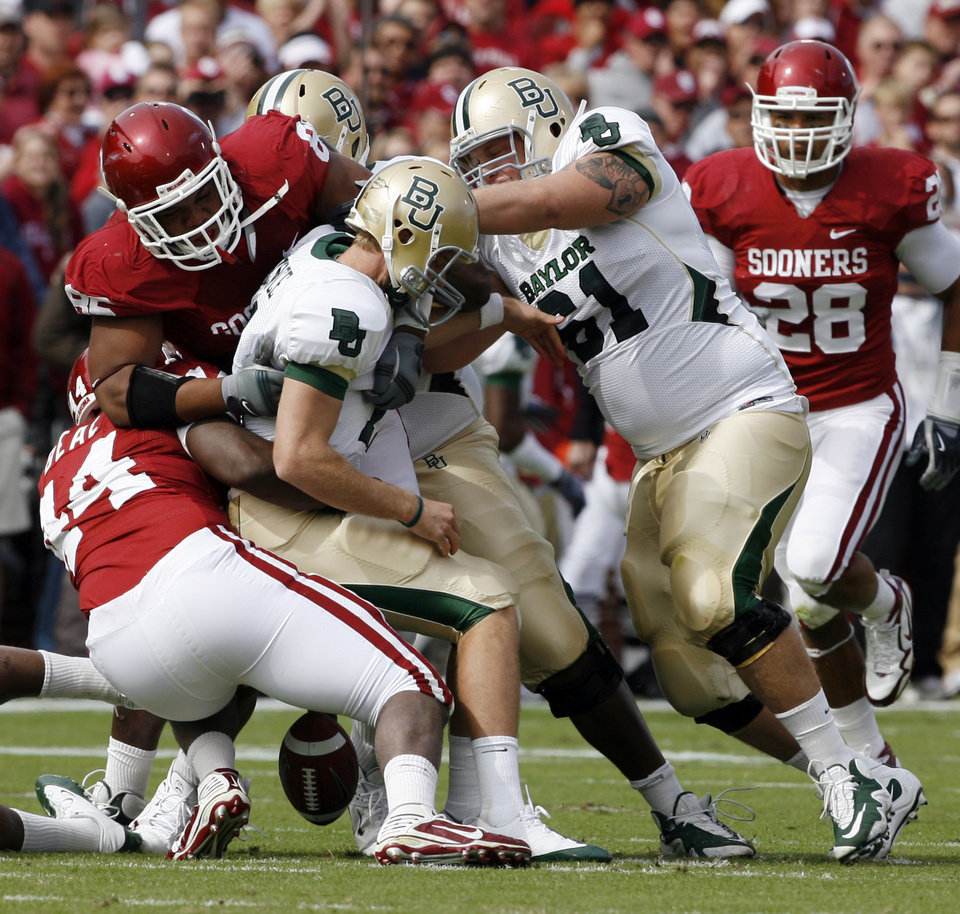Photo - Jeremy Beal (44) and James Winchester (86) sack reserve quarterback Blake Szymanski causing a fumble during the first half of the college football game between The University of Oklahoma Sooners (OU) and the Baylor Bears at the Gaylord Family-Oklahoma Memeorial Stadium on Saturday, Oct. 10, 2009, in Norman, Okla.