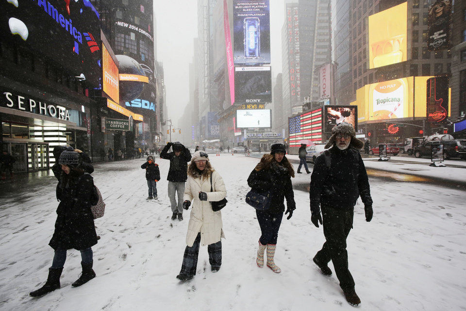 Photo - Pedestrians make their way through a snowfall, Tuesday, Jan. 21, 2014 in New York's Times Square. A storm is sweeping across the Mid-Atlantic and New England. The National Weather Service said the storm could bring 8 to 12 inches of snow to Philadelphia and New York City, and more than a foot in Boston. Bitterly cold air with wind chills as low as 10 degrees below zero was forecast. (AP Photo/Mark Lennihan)