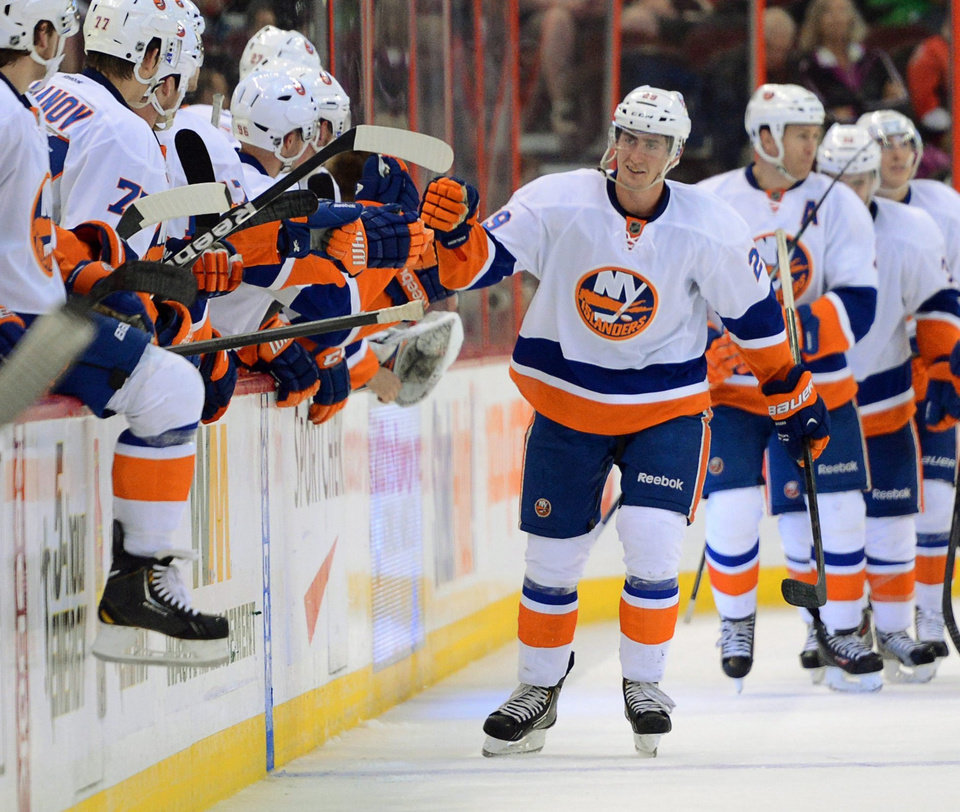 Photo - New York Islanders' Brock Nelson skates past the bench for hi-fives after scoring a second period goal against the Ottawa Senators during pre-season NHL hockey action in Ottawa, Ontario, on Sunday, Sept. 29, 2013.  (AP Photo/The Canadian Press, Sean Kilpatrick)