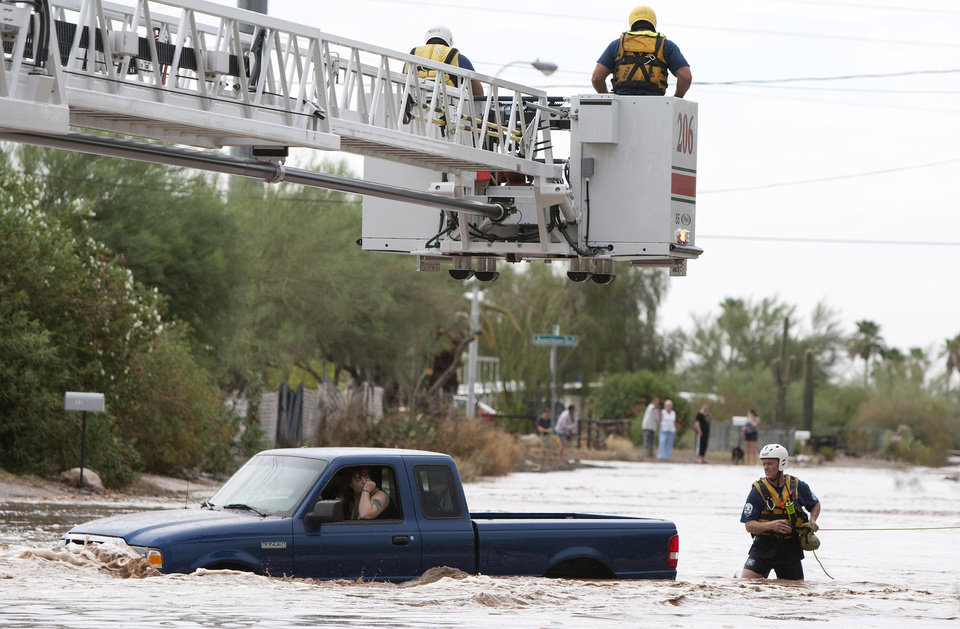 Photo - A man and woman sit in a truck on Tomahawk Rd. flooded by rain waters in Apache Junction, Ariz., Sunday, July 21, 2013. Mesa Fire Dept. were able to walk the two out safely. (AP Photo/The Arizona Republic, Cheryl Evans)