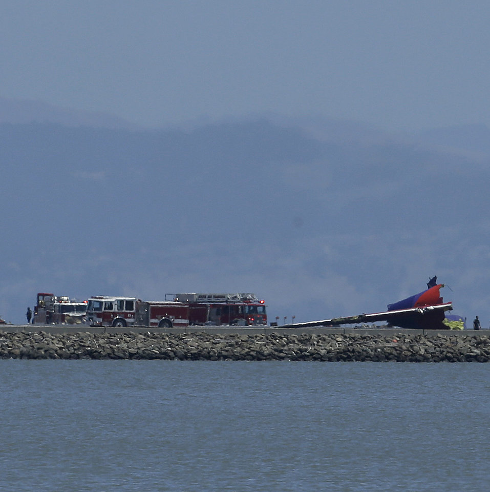 Photo - The tail of Asiana Flight 214 is seen, right, after it crashed at San Francisco International Airport in San Francisco, Saturday, July 6, 2013. (AP Photo/Jeff Chiu)