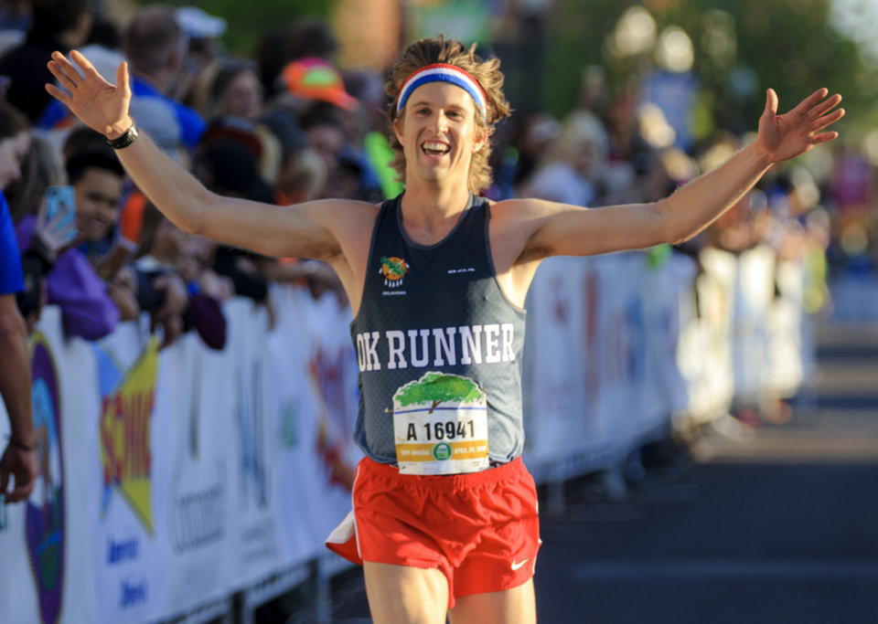Photo - Andrew Leahey reacts as he crosses the finish line for the half marathon during the Oklahoma City Marathon in Oklahoma City, Okla. on Sunday, April 29, 2018.  . Photo by Chris Landsberger, The Oklahoman