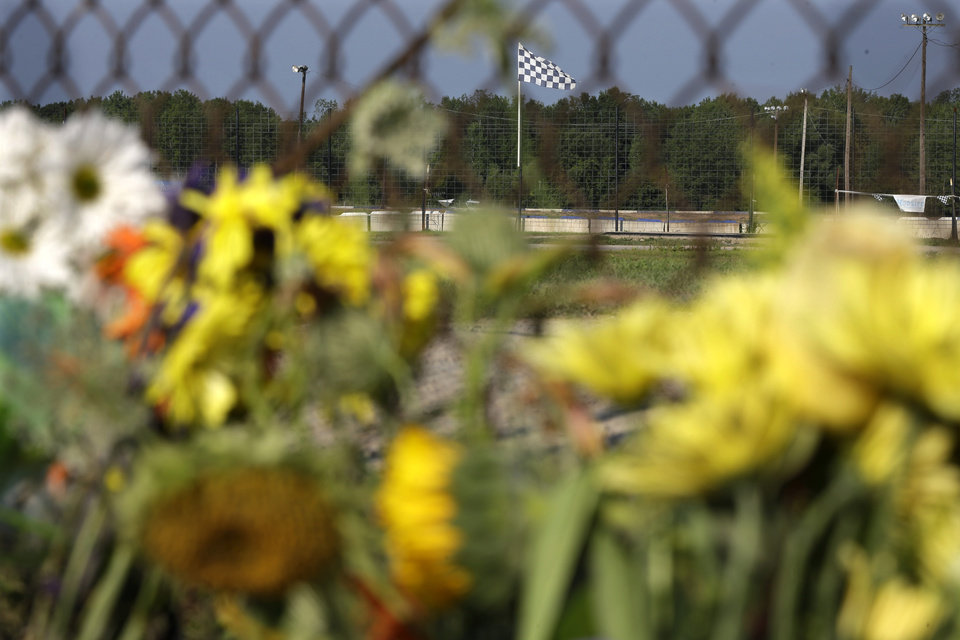 Photo - A checkered flag flies over the track near a small memorial of flowers at Canandaigua Motorsports Park Monday, Aug. 11, 2014, in Canandaigua, N.Y. On Saturday night, Tony Stewart struck and killed Kevin Ward Jr., 20, a sprint car driver who had climbed from his car and was on the track trying to confront Stewart during a race at the track in upstate New York. Ontario County Sheriff Philip Povero said his department's investigation is not criminal and that Stewart was