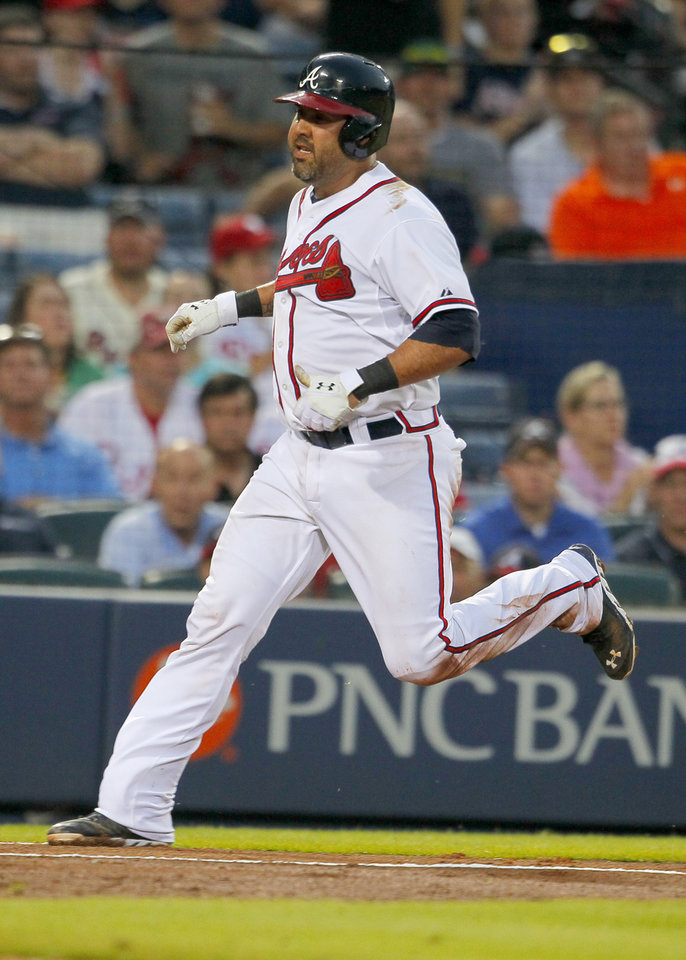 Photo - Atlanta Braves Gerald Laird (11) scores from a double hit by Jason Heyward (22) in the fifth inning of a baseball game against the Philadelphia Phillies Tuesday, June 17, 2014, in Atlanta. (AP Photo/Todd Kirkland)