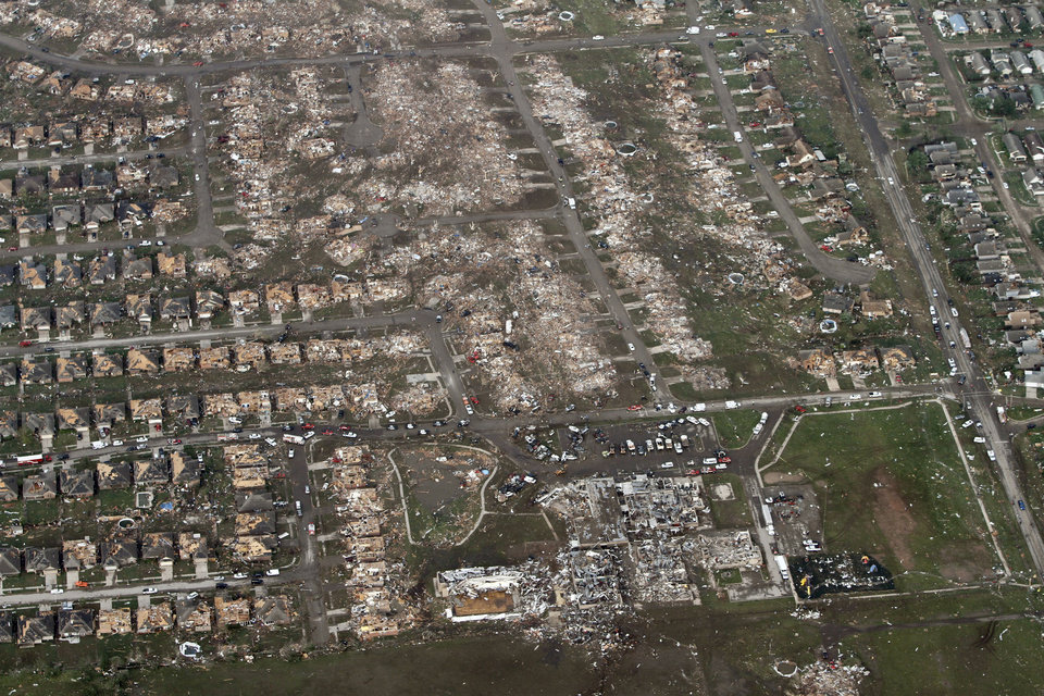 Photo -  This aerial photo shows the remains of homes hit by a massive tornado in Moore, Okla., Monday May 20, 2013. A tornado roared through the Oklahoma City suburbs Monday, flattening entire neighborhoods, setting buildings on fire and landing a direct blow on an elementary school. (AP Photo/Steve Gooch) ORG XMIT: OKOKL109