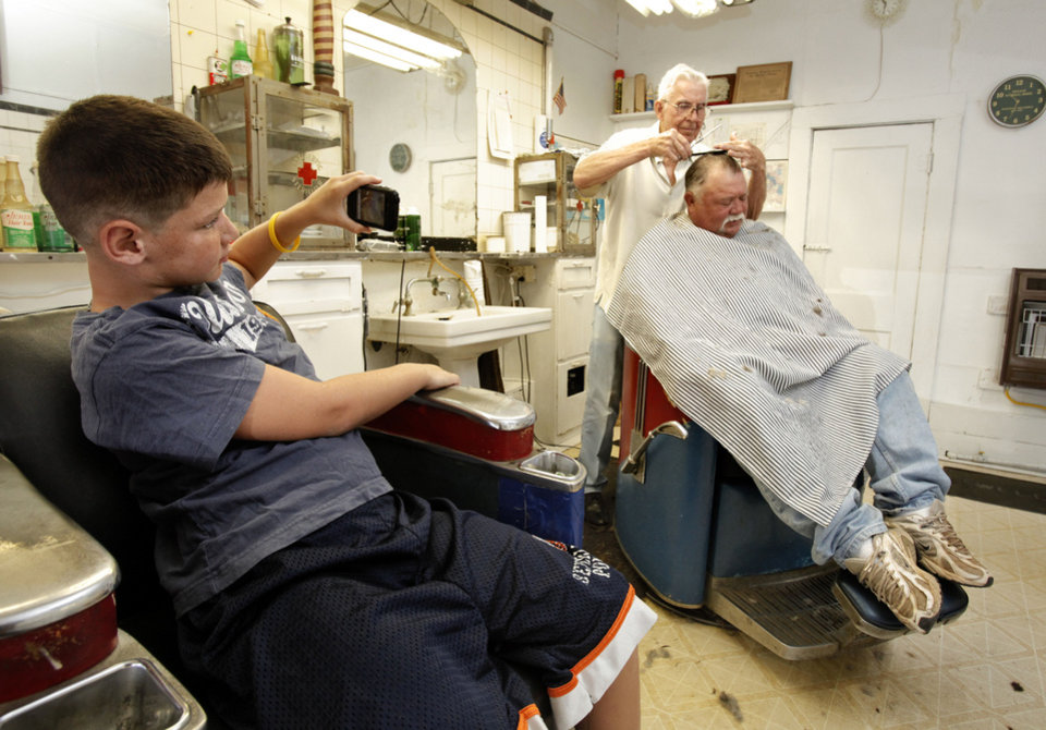 Colby Wyatt, 8, records events on a cellphone as John �Dugan� Adkins cuts Colby�s grandfather Paul Arnold�s hair Tuesday in Maysville. Arnold, who has been coming to Adkins since he was 3, brought Colby and his  brother Kaedon into the shop for a haircut as well. Photo by Steve Sisney, The Oklahoman