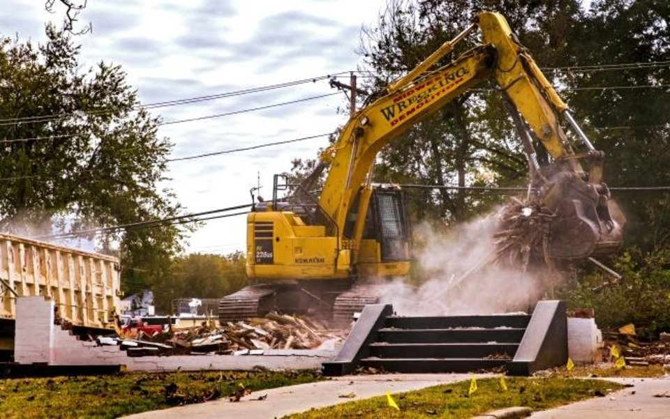 Photo -  Crews demolish a home located at 1116 NW 13 St. where a new OnCue will be built. [CHRIS LANDSBERGER/THE OKLAHOMAN]