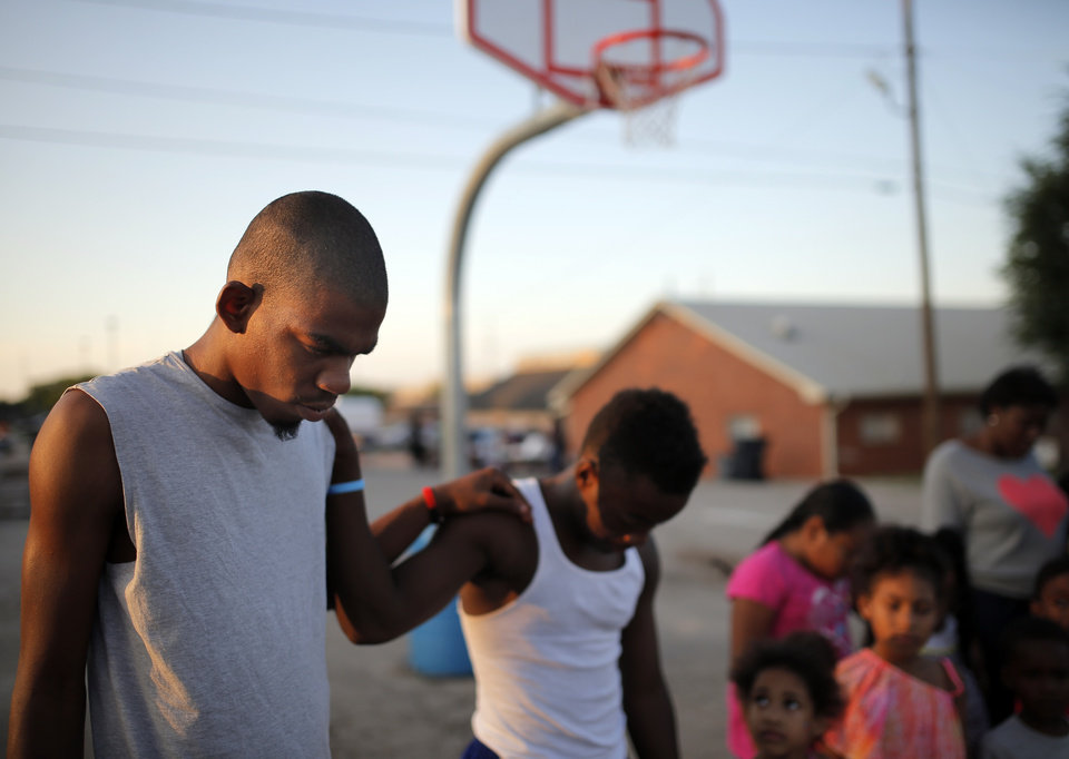 Photo -  Tyrell Bagby, left, and Tayonte Bagby pray. Photos by Sarah Phipps, The Oklahoman   SARAH PHIPPS -  SARAH PHIPPS