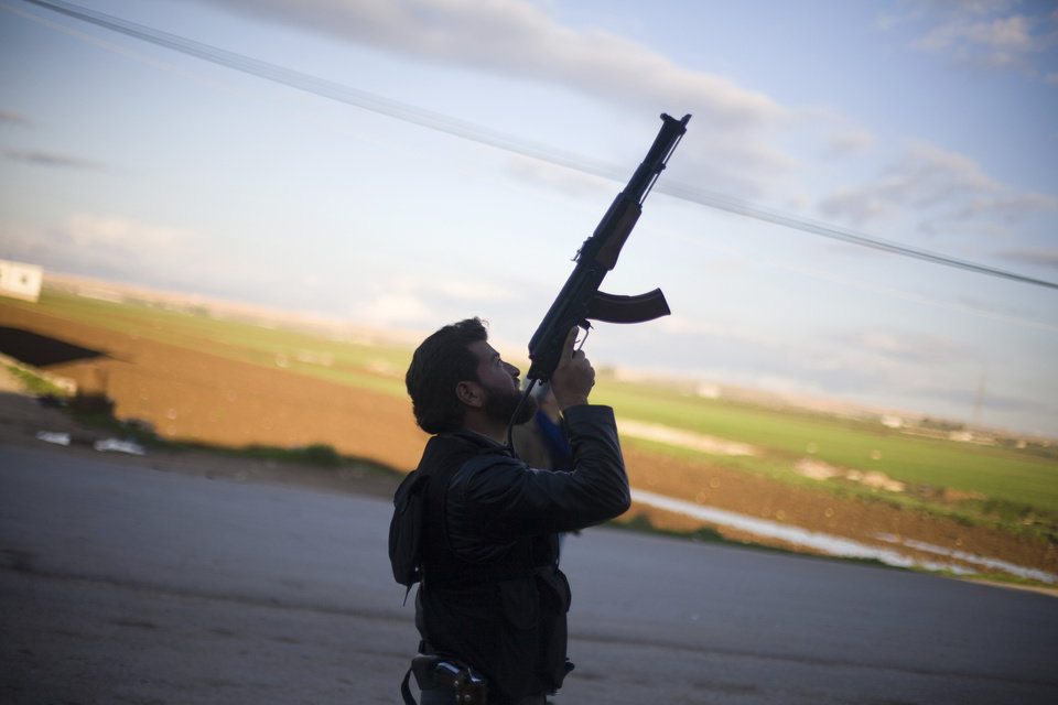 A Free Syrian Army fighter points his weapon as he watches a Syrian Army jet, not pictured, in Fafeen village, north of Aleppo province, Syria, Tuesday, Dec. 11, 2012. (AP Photo/Manu Brabo)  ORG XMIT: CAI115