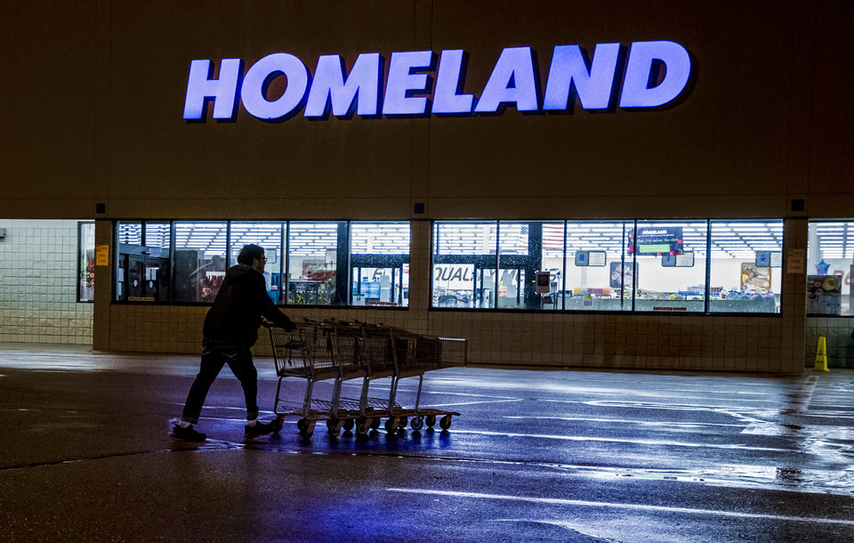 Photo - A crew member pushes shopping carts in from the parking lot at the Homeland grocery store located at 11241 W. Reno Ave. in Yukon, Okla. on Thursday, March 19, 2020. Homeland has dedicated the first hour of store operations to senior customers and those who have medical conditions that put them at risk from COVID-19.  [Chris Landsberger/The Oklahoman]