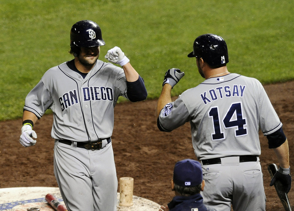 Photo - San Diego Padres' Mark Kotsay, right, congratulates teammate Jaff Decker after Decker hit a solo home run in the seventh inning of a baseball game against the Colorado Rockies on Monday, Aug. 12, 2013, in Denver. (AP Photo/Chris Schneider)