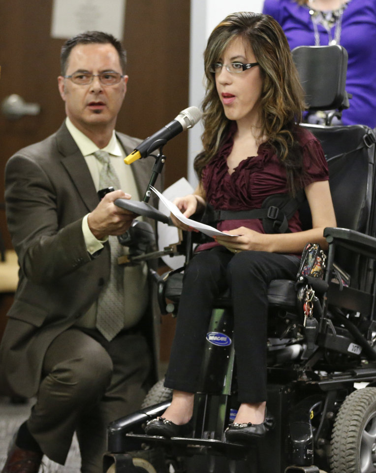 Aracely Baeza, right, a 23-year-old with a rare form of muscular dystrophy, speaks before a meeting of the Oklahoma Health Care Authority in Oklahoma City, Tuesday, July 1, 2014. Baeza, a recent college graduate, spoke about how she depends on her specialized wheelchair to be independent. Holding a microphone for her at left is Rich Salm. The Board unanimously approved a 7.75 percent provider rate cut during a special meeting as it grapples with a $104 million hole in its budget for the new fiscal year.(AP Photo/Sue Ogrocki)