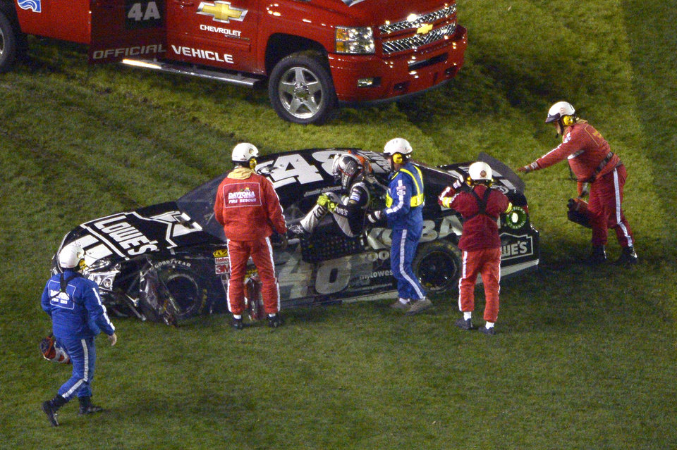 Photo - Jimmie Johnson is helped out of his car after it colliding with the inside wall on the front stretch during the Sprint Unlimited auto race at Daytona International Speedway in Daytona Beach, Fla., Saturday, Feb. 15, 2014. (AP Photo/Phelan M. Ebenhack)