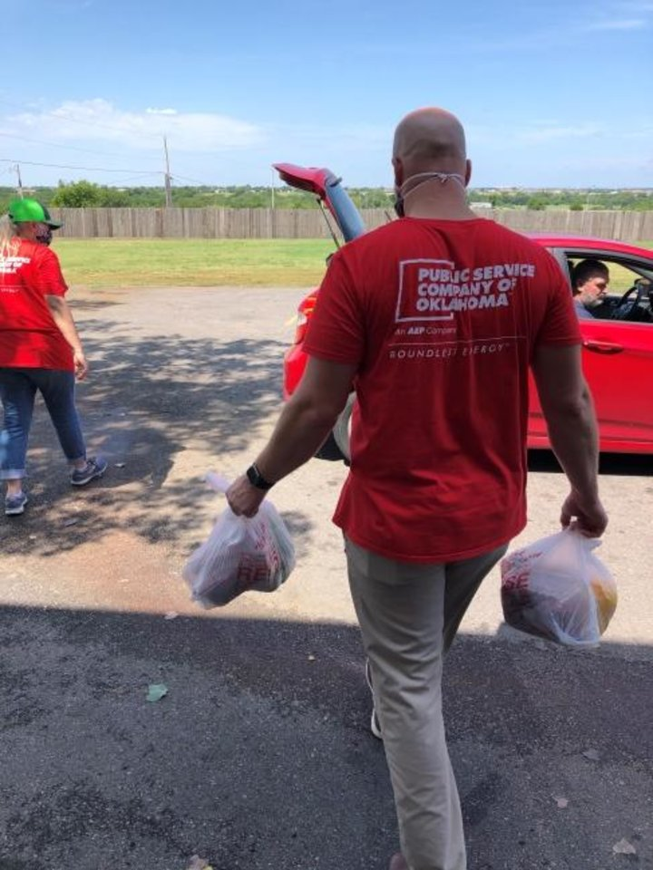 Photo -  Public Service Co. of Oklahoma volunteers help distribute food recently at the Lawton Food Bank. The utility also was providing a four-pack of energy efficient LEDs to each of the organization's clients. [PROVIDED BY PUBLIC SERVICE CO. OF OKLAHOMA]