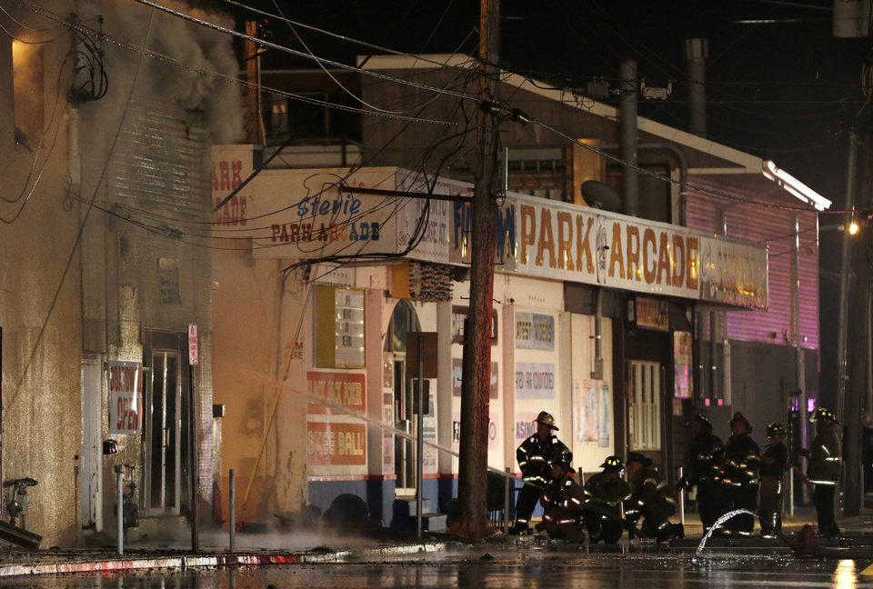 Photo - Firefighters battle a blaze in a building on the Seaside Park boardwalk on Thursday, Sept. 12, 2013, in Seaside Park, N.J. The fire began in a frozen custard stand on the Seaside Park section of the boardwalk and quickly spread north into neighboring Seaside Heights. (AP Photo/Julio Cortez)