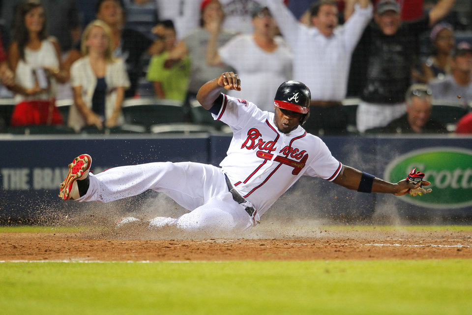 Photo - Atlanta Braves Justin Upton (8) slides in to score in the ninth inning of a baseball game against the Philadelphia Phillies Monday, June 16, 2014, in Atlanta. (AP Photo/Todd Kirkland)