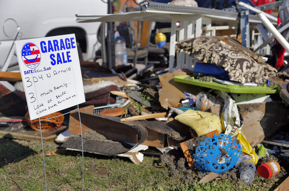 Photo - Storm debris starts to surround a garage sale sign as residents clean up storm damage to a home in Moore, Okla. on Thursday, March 26, 2015. A tornado hit the area on Wednesday evening causing damage in the area.  Photo by Chris Landsberger, The Oklahoman