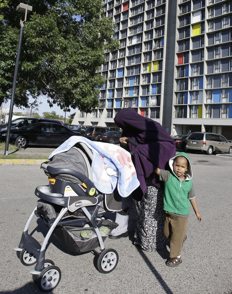 In this photo taken Tuesday, Sept. 24, 2013, a young Somali boy accompanies  his mother who covers her head to avoid being photographed by the high rise where many Somali people live in Minneapolis. It's been six years since Minnesota first began furnishing young fighters to al-Shabab, the terror group that has claimed responsibility for the deadly mall attack in Kenya. (AP Photo/Jim Mone)