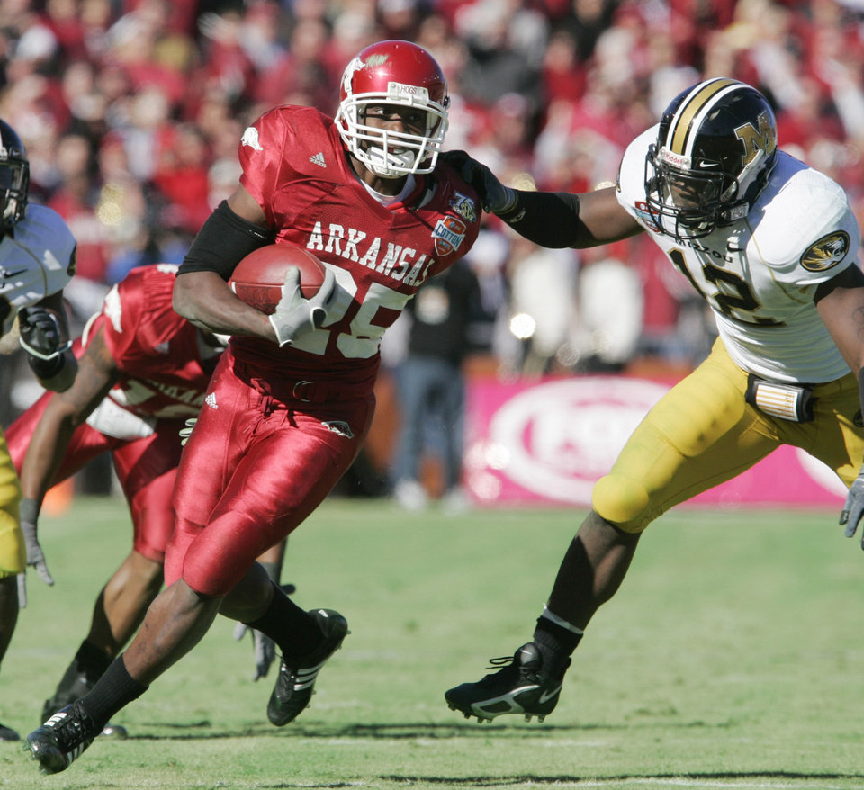Photo - ** FILE ** In this Jan. 1, 2008 file photo, University of Arkansas tailback Felix Jones (25) pulls away from Missouri linebacker Sean Weatherspoon (12) as he rushes for 23 yards in the second quarter of the Cotton Bowl college football game in Dallas. Jones is a top prospect in the upcoming 2008 NFL football draft on Saturday, April 26, 2008. (AP Photo/Donna McWilliam, File) ORG XMIT: NY249