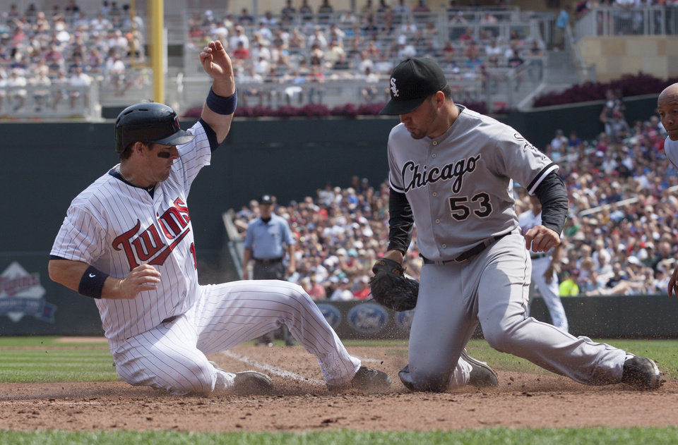 Minnesota Twins' Josh Willingham, left, is tagged out by Chicago White Sox starting pitcher Hector Santiago (53) after trying to score from third on a passed ball during the fourth inning of a baseball game on Sunday, Aug. 18, 2013, in Minneapolis. (AP Photo/Paul Battaglia)