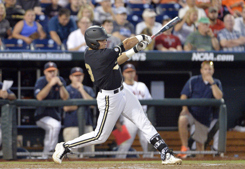 Photo - Vanderbilt's Vince Conde hits an RBI single against Virginia in the sixth inning of Game 3 of the best-of-three NCAA baseball College World Series finals in Omaha, Neb., Wednesday, June 25, 2014. (AP Photo/Ted Kirk)