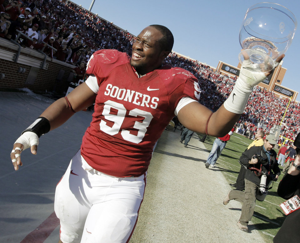 Photo - OU's Gerald McCoy (93) celebrates with the trophy after the Bedlam college football game between the University of Oklahoma Sooners (OU) and the Oklahoma State University Cowboys (OSU) at the Gaylord Family-Oklahoma Memorial Stadium on Saturday, Nov. 28, 2009, in Norman, Okla. OU won, 27-0.Photo by Nate Billings, The Oklahoman