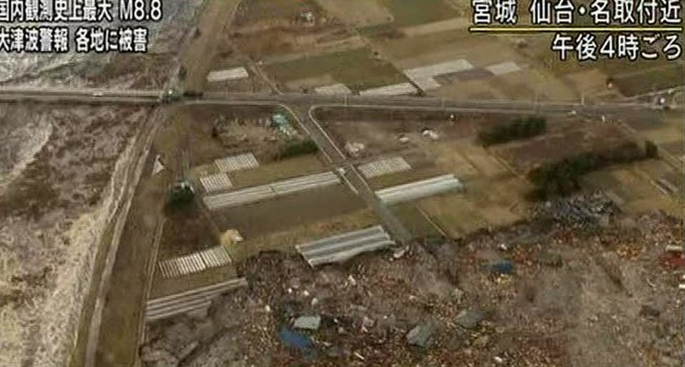 Photo - In this video image taken from Japan's NHK TV, houses, cars and debris half submerged is swept towards a highway by a tsunami in the Sendai city area, Miyagi Prefecture (state) after Japan Friday March 11, 2011 following a massive earth quake. A magnitude 8.9 earthquake slammed Japan's northeastern coast Friday, unleashing a 13-foot (4-meter) tsunami that swept boats, cars, buildings and tons of debris miles inland. Fires triggered by the quake burned out of control up and down the coast.  (AP PHOTO/NHK TV) MANDATORY CREDIT, JAPAN OUT, TV OUT,  NO SALES, EDITORIAL USE ONLY ORG XMIT: LON817