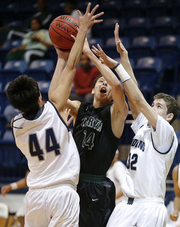 Photo - Norman North's Lindy Waters III goes to the basket between El Reno's Christian Wassana, left, and Kade Hileman on Friday. Photo by Bryan Terry, The Oklahoman