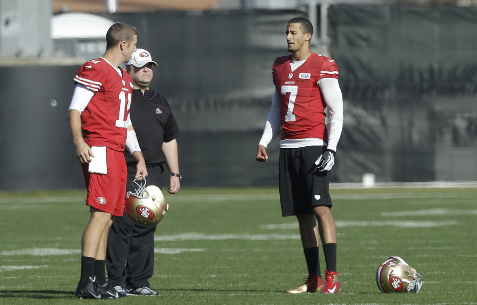 Photo - San Francisco 49ers quarterback Colin Kaepernick (7) talks with quarterback Alex Smith (11) and offensive coordinator Greg Roman during practice at an NFL football training facility in Santa Clara, Calif., Friday, Jan. 25, 2013. The 49ers are scheduled to play the Baltimore Ravens in the Super Bowl on Sunday, Feb. 3. (AP Photo/Jeff Chiu)