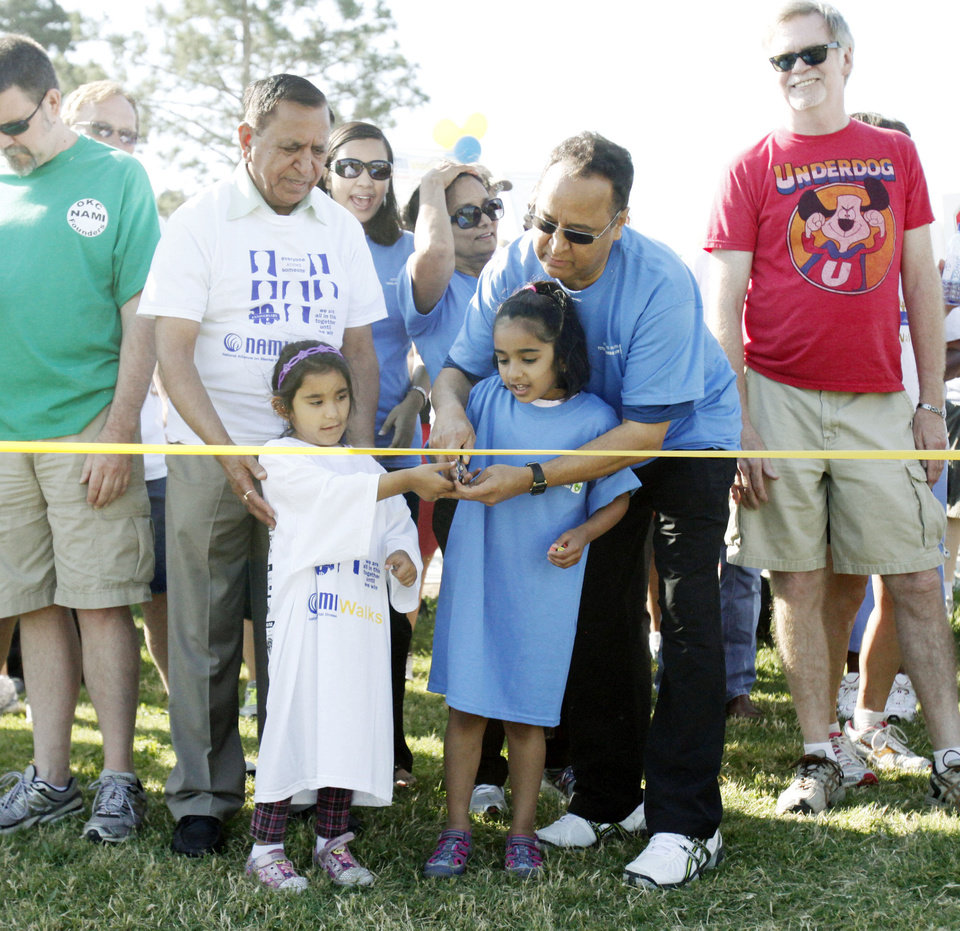 Photo - Kailash Sachdeva and his granddaughter Diviya (left) along with Dr. R. Murali Krishna and his granddaughter Leela Walia, cut the ribbon to begin the NAMI (National Alliance on Mental Illness) walk at Stars and Stripes Park in Oklahoma City, OK, to raise money for mental illness causes, Saturday, May 19, 2012,  By Paul Hellstern, The Oklahoman