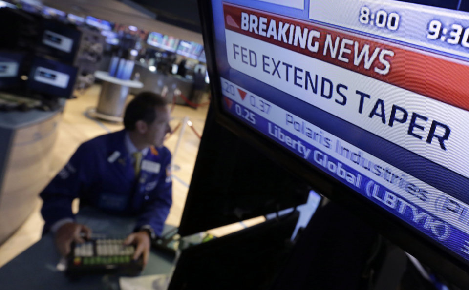 Photo - A television monitor at a trading post on the floor of the New York Stock Exchange shows the decision of the Federal Reserve, Wednesday, June 18, 2014. The Federal Reserve says it will further slow the pace of its bond purchases because a strengthening U.S. job market needs less support. But it's offering no clear signal about when it will start raising its benchmark short-term rate.  (AP Photo/Richard Drew)