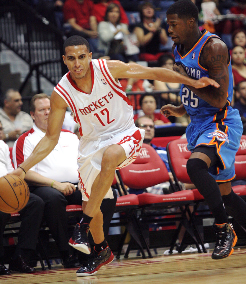 Houston Rockets' Kevin Martingets (12) dribbles past Oklahoma City Thunder's DeAndre Liggins during the second quarter of an NBA preseason basketball game in Hidalgo, Texas, Wednesday, Oct. 10, 2012. (AP Photo/Delcia Lopez) ORG XMIT: TXDL111