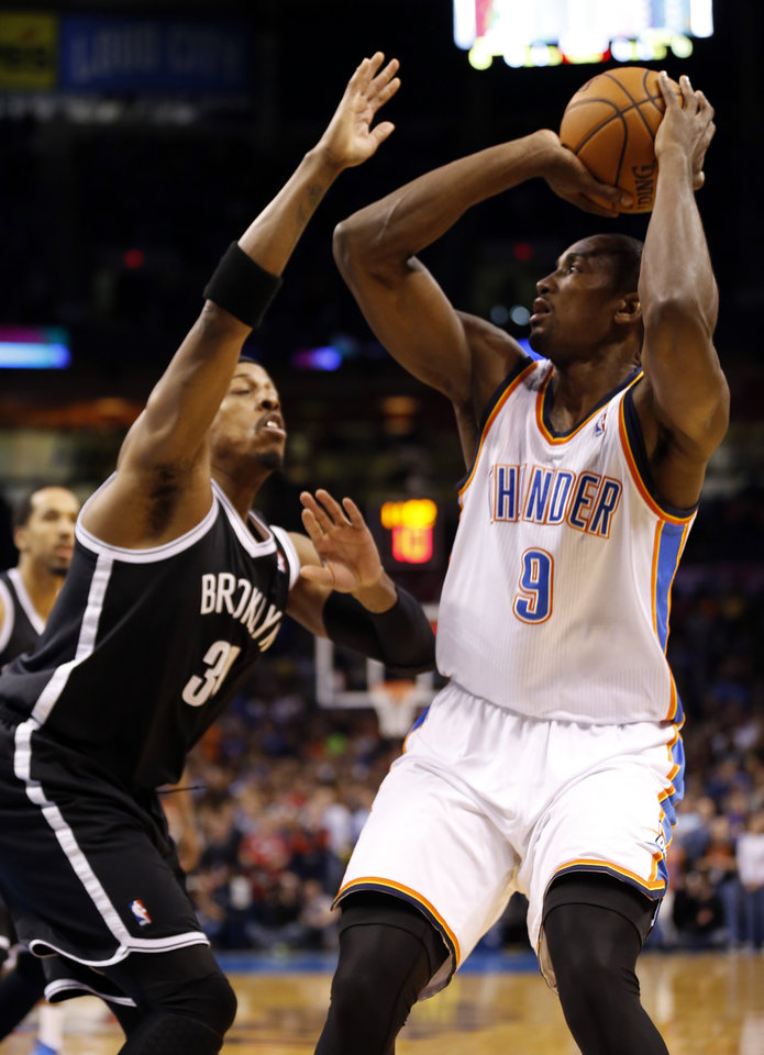 Photo - Thunder's Serge Ibaka (9) shoots over Brooklyn's Paul Pierce (34) in the NBA basketball game where the Oklahoma City Thunder were defeated 95-93 by the Brooklyn Nets at the Chesapeake Energy Arena in Oklahoma City, on Thursday, Jan. 2, 2014. Photo by Steve Sisney, The Oklahoman