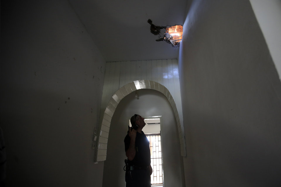 Photo - An Israeli policeman examines the hole in the roof damaged after a rocket fired from Gaza hit in a residential neighborhood of the southern city of Sderot, Israel, Friday, August 8, 2014. (AP Photo/Tsafrir Abayov)