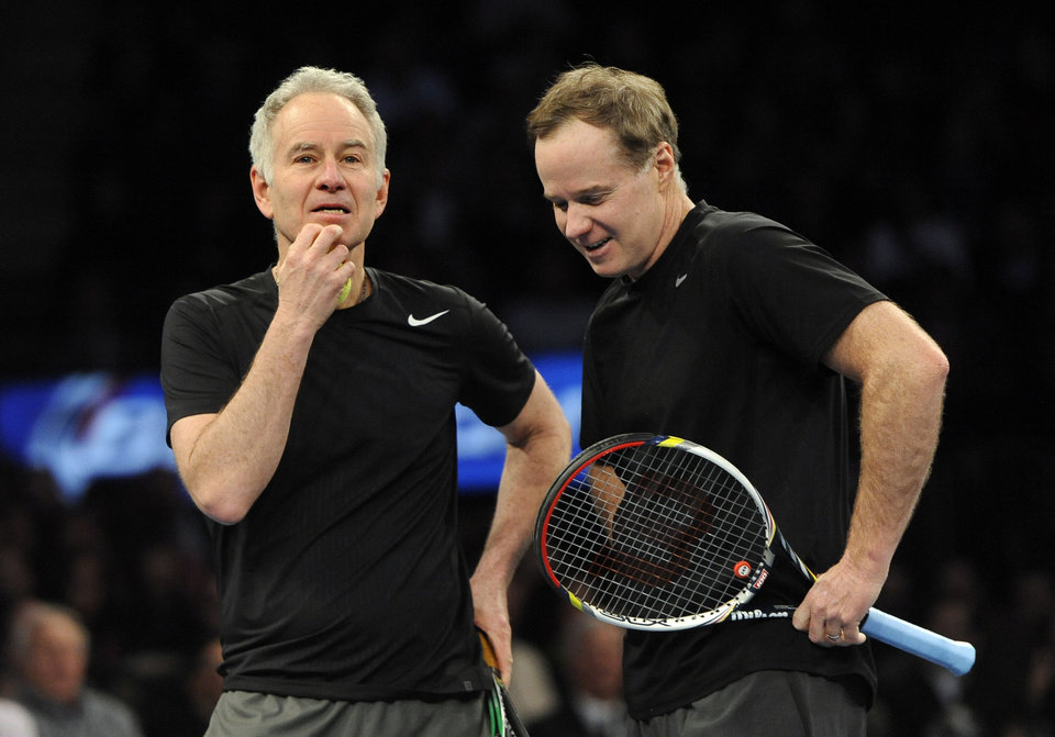 Photo - John, left, and Patrick McEnroe confer during their match against Mike and Bob Bryan in the BNP Paribas Showdown Tennis Tournament on Monday, March 3, 2014, in New York. The Bryans won 8-3. (AP Photo/Kathy Kmonicek)