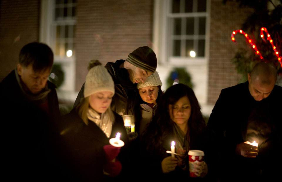 Photo - Brian Tenenhaus, center left, comforts Lauren Foster, during a candlelight vigil outside the Edmond Town Hall, Saturday, Dec. 15, 2012, in Newtown, Conn.  A gunman walked into Sandy Hook Elementary School in Newtown Friday and opened fire, killing 26 people, including 20 children. (AP Photo/David Goldman) ORG XMIT: CTDG154