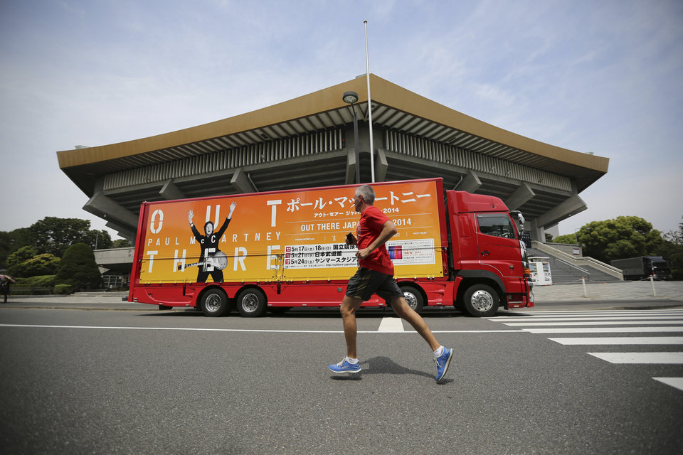 Photo - A man jogs in front of an advertising truck bearing an image of Paul McCartney at Nippon Budokan hall in Tokyo, Tuesday, May 20, 2014. Paul McCartney is canceling his entire Japan tour because of illness including the one set for Wednesday at Nippon Budokan hall, where The Beatles performed during their first Japan tour in 1966. (AP Photo/Eugene Hoshiko)
