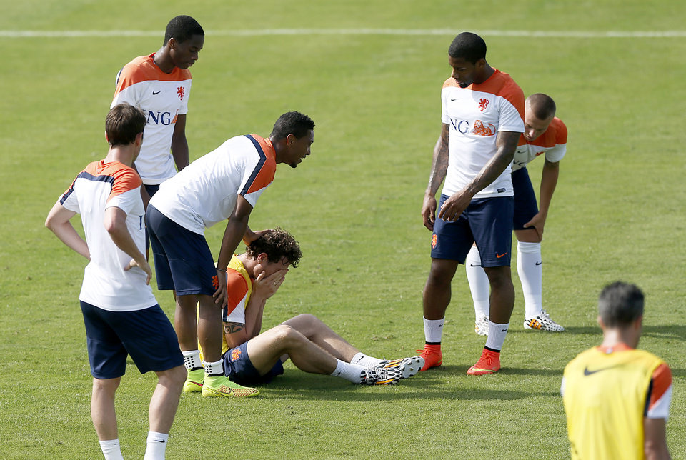 Photo - Daryl Janmaat, center, falls after clashing with Jonathan de Guzman, third right, of the Netherlands, during a training session in Rio de Janeiro, Brazil, Thursday, June 26, 2014.  Netherlands will play Group A runner-up Mexico in the second round on Sunday in Fortaleza. (AP Photo/Wong Maye-E)