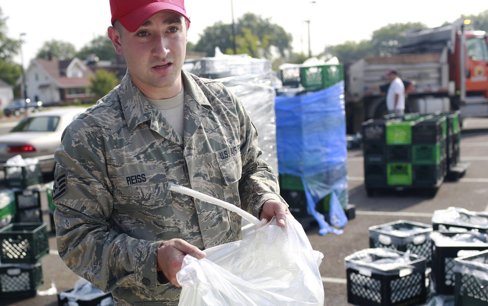 Photo - A member of the Ohio Air National Guard carries a bag of water to a nearby car, Sunday, Aug. 3, 2014, at Woodward High School in Toledo, Ohio. More tests are needed to ensure that toxins are out of Toledo's water supply, the mayor said Sunday, instructing the 400,000 people in the region to avoid drinking tap water for a second day. Toledo officials issued the warning early Saturday after tests at one treatment plant showed two sample readings for microsystin above the standard for consumption, possibly because of algae on Lake Erie. (AP Photo/Haraz N. Ghanbari)
