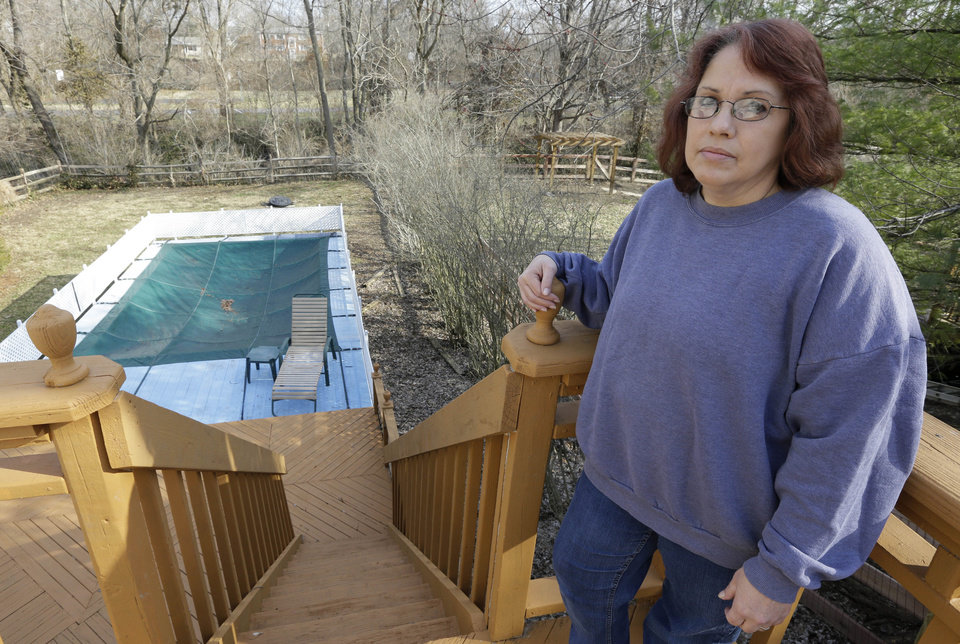 Photo - Regina Bachman stands on her deck overlooking her backyard and a small creek that runs behind her home in Loveland, Ohio on Friday, March 21, 2014. Bachman bought the home in September 2013 and was initially told by the bank that flood insurance on the property would be affordable, only to find out after closing that the rates were going to increase over $7,000 more annually with new premiums for the National Flood Insurance Program. (AP Photo/Al Behrman)