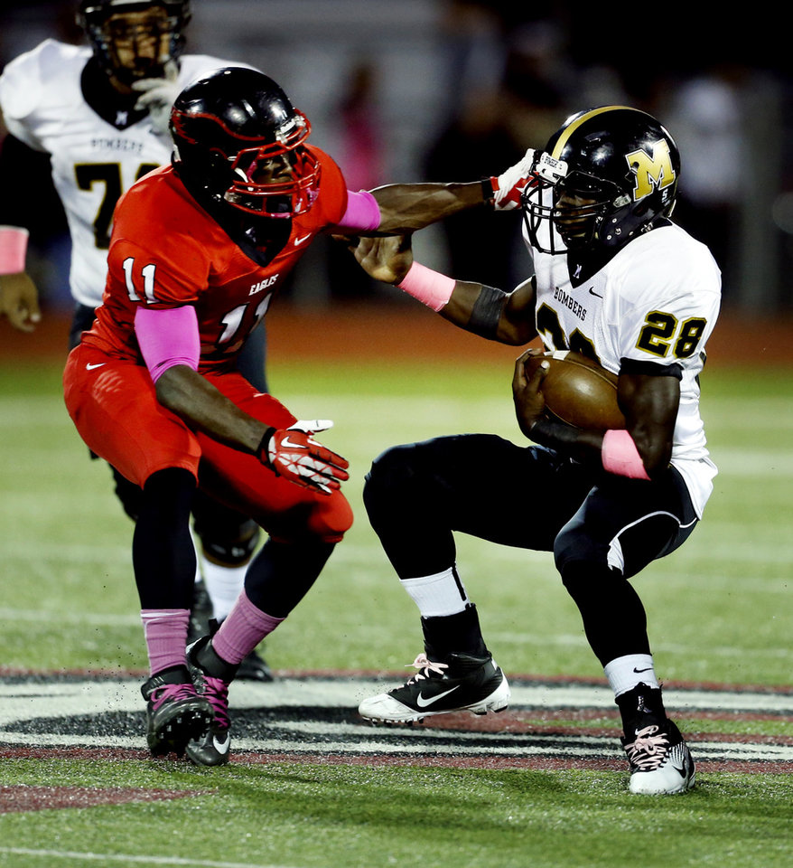 Midwest City's Tre'jon Sherffield (28) tries to get past Del City's Xaviar Sanders in high school football on Friday, Sept. 20, 2013 in Del City, Okla.  Photo by Steve Sisney, The Oklahoman