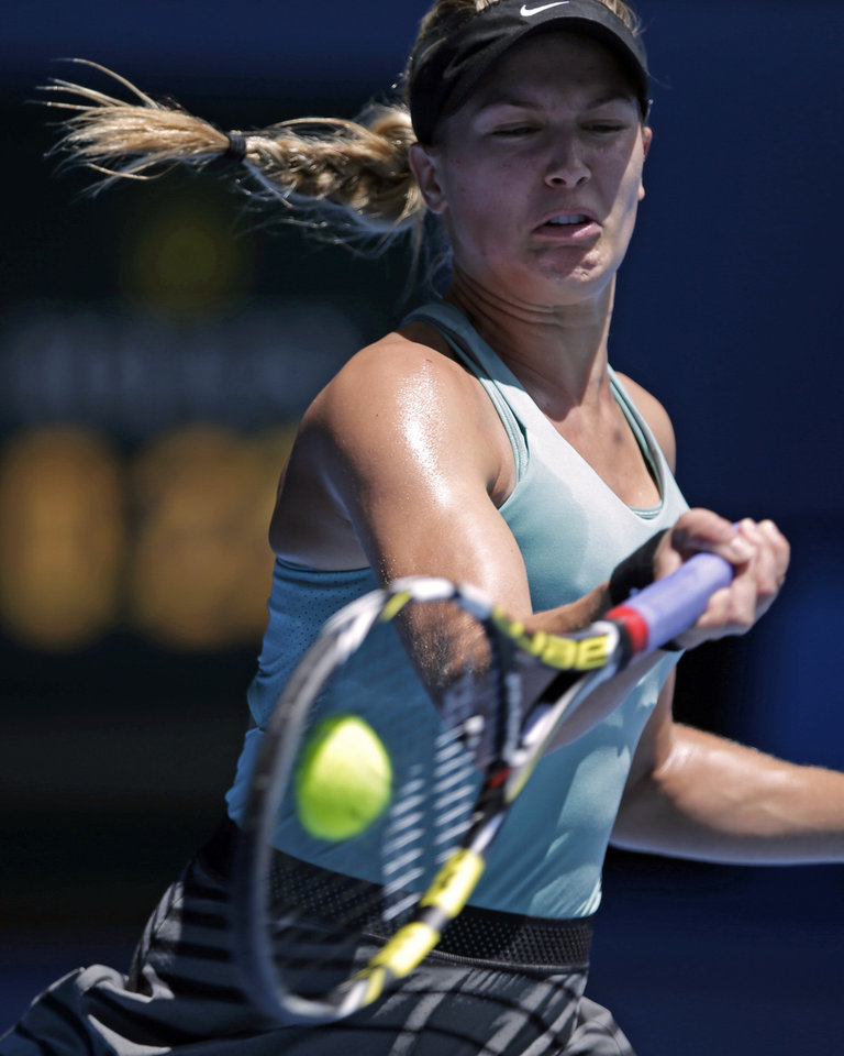 Photo - Eugenie Bouchard of Canada makes a forehand return to Ana Ivanovic of Serbia during their quarterfinal at the Australian Open tennis championship in Melbourne, Australia, Tuesday, Jan. 21, 2014. (AP Photo/Rick Rycroft)