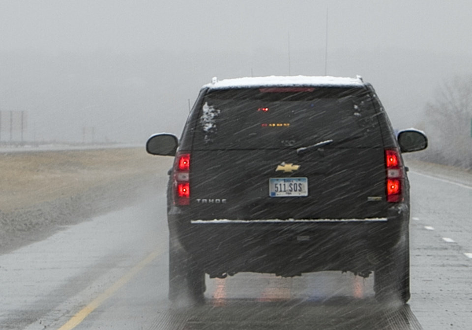 Photo - FILE - In this Nov. 2, 2011, file photo is a black SUV, with a license plate that is not on file in police databases, carrying Iowa Gov. Terry Branstad. State data shows that more than 3,200 license plates have been issued to local, state and federal agencies with a designation that allows them to avoid tickets from Iowa traffic cameras. (AP Photo/Nati Harnik, File)