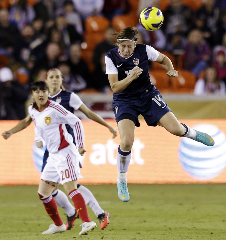 United States' Abby Wambach (14) heads a ball in front of China's Huang Yini during the second half of an exhibition soccer match, Wednesday, Dec. 12, 2012, in Houston. (AP Photo/David J. Phillip)