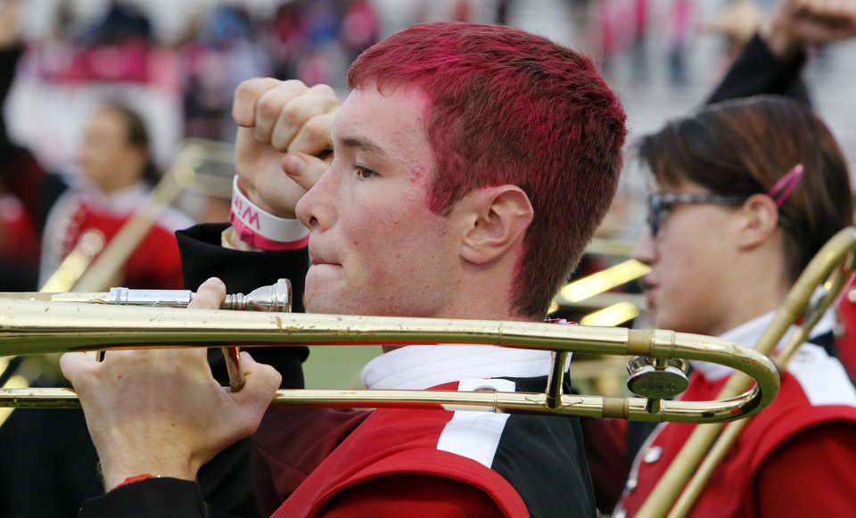 Photo - Del City band trombone player David Terry wears pink hair to support win win week as the Del City Eagles play the Midwest City Bombers in high school football on Friday, Sept. 20, 2013 in Del City, Okla.  Photo by Steve Sisney, The Oklahoman