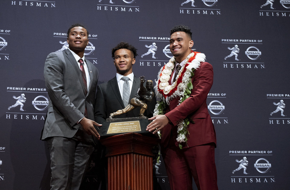 Photo - Heisman Trophy finalists, from left, Dwayne Haskins, from Ohio State; Kyler Murray, from Oklahoma; and Tua Tagovailoa, from Alabama, pose with the tophy during a media event Saturday, Dec. 8, 2018, in New York. (AP Photo/Craig Ruttle)