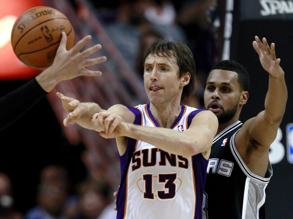 Photo -   Phoenix Suns' Steve Nash (13) passes as San Antonio Spurs' Patty Mills, of Australia, defends during the first half of an NBA basketball game, Wednesday, April 25, 2012, in Phoenix. (AP Photo/Matt York)
