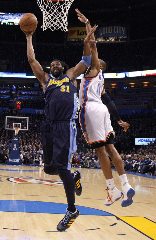 Denver's Nene (31) dunks over Oklahoma City's Russell Westbrook (0)during the NBA basketball game between the Denver Nuggets and the Oklahoma City Thunder in the first round of the NBA playoffs at the Oklahoma City Arena, Wednesday, April 27, 2011. Photo by Sarah Phipps, The Oklahoman