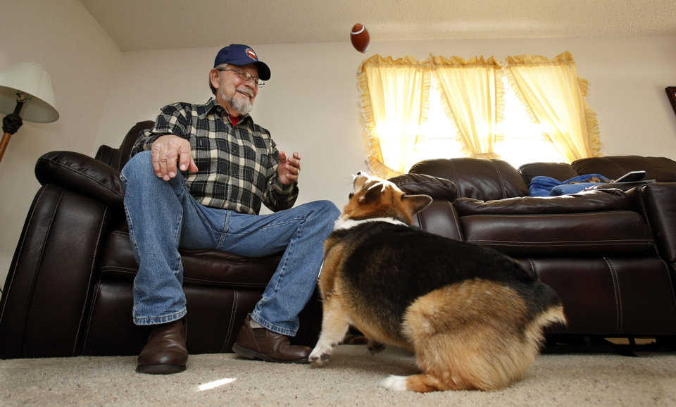 Barry Sanders, 70, plays football with his six-year-old corgi Rollie at his home on Thursday, Jan. 17, 2013, in Blanchard, Okla. He has the same name as a sports celebrity. Photo by Steve Sisney, The Oklahoman STEVE SISNEY - THE OKLAHOMAN