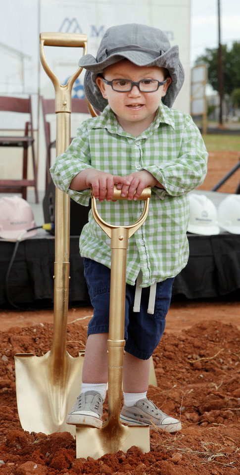 Brock Hart, 3, of Edmond, plays with one of the shovels before groundbreaking ceremonies for the OK Kids Korral.